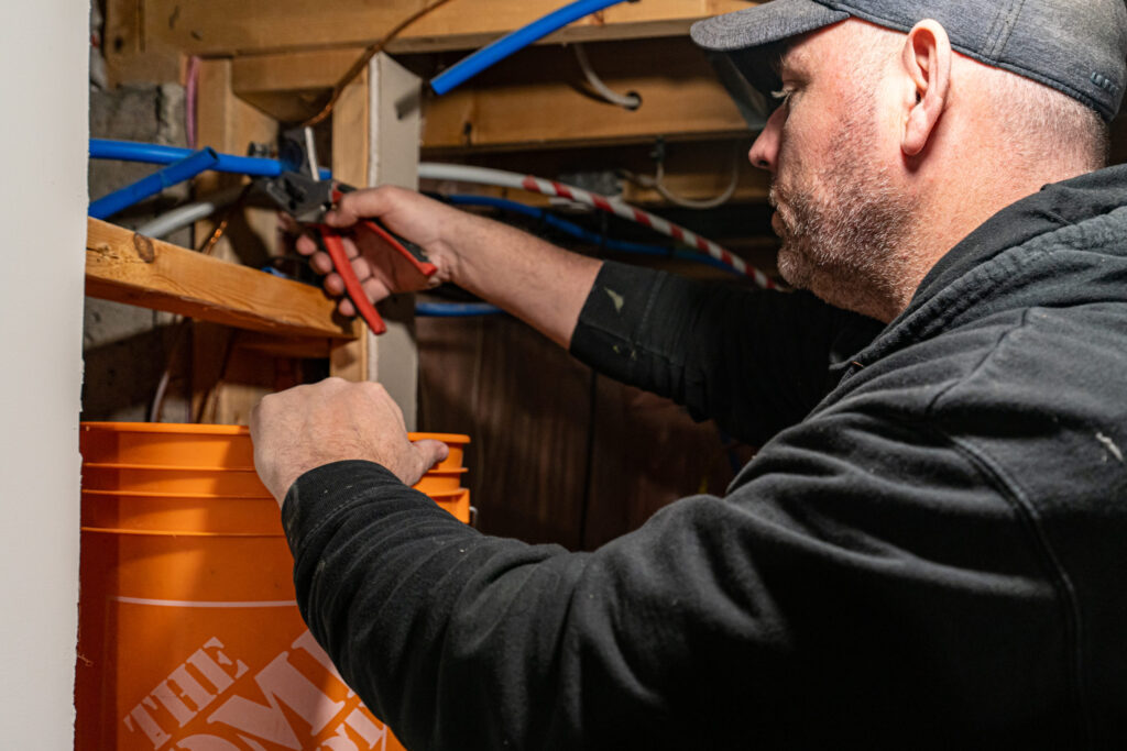 licensed plumber cutting pipe for replacement